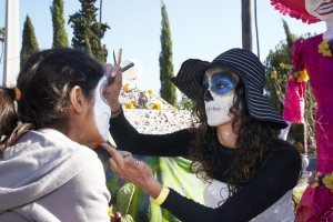 Woman paints girls face at Day of the Dead (Dia de los Muertos) at Hollywood Forever cemetery