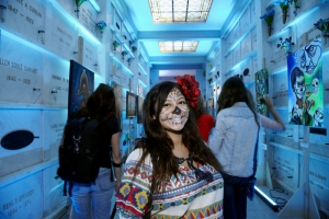 Woman in costume stands in mausoleum at Day of the Dead (Dia de los Muertos) at Hollywood Forever cemetery