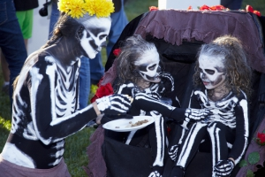 Mother dressed like a skeleton offers food to her twin girls also dressed like skeletons at  Day of the Dead (Dia de los Muertos) at Hollywood Forever cemetery