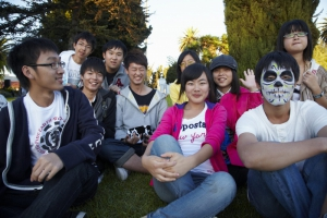 Group of Japanese students laugh  together at Day of the Dead (Dia de los Muertos) at Hollywood Forever cemetery